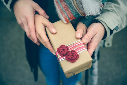 Closeup of woman and man hands showing a gift box with red handmade flowers otdoors in a cold autumn day. Love and couple relationships concept.